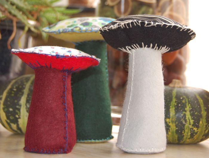 3 paddenstoelen gemaakt van vilt  en stof tussen de pompoenen en kastanjes van de herfsttafel van opzij - studio paars