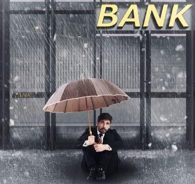 uomo seduto fuori dalla sede di una banca