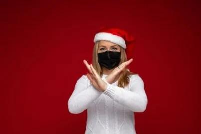 donna con mascherina e cappello di babbo Natale incrocia le braccia