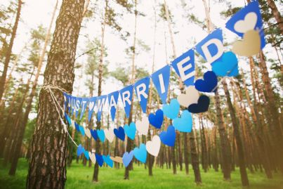 scritta oggi sposi appesa a due alberi