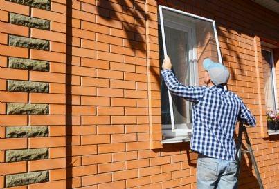 uomo che monta zanzariera sulla finestra