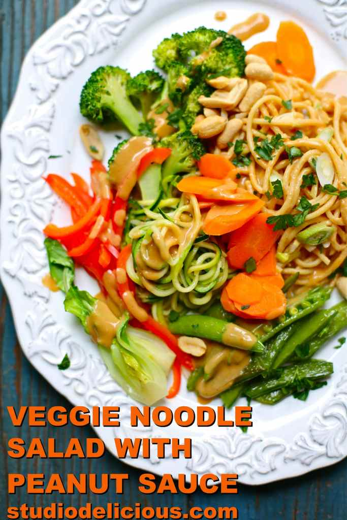 Broccoli, peanutes, red pepper, snap peas and zuchinni and noodles on a white plate with blue background