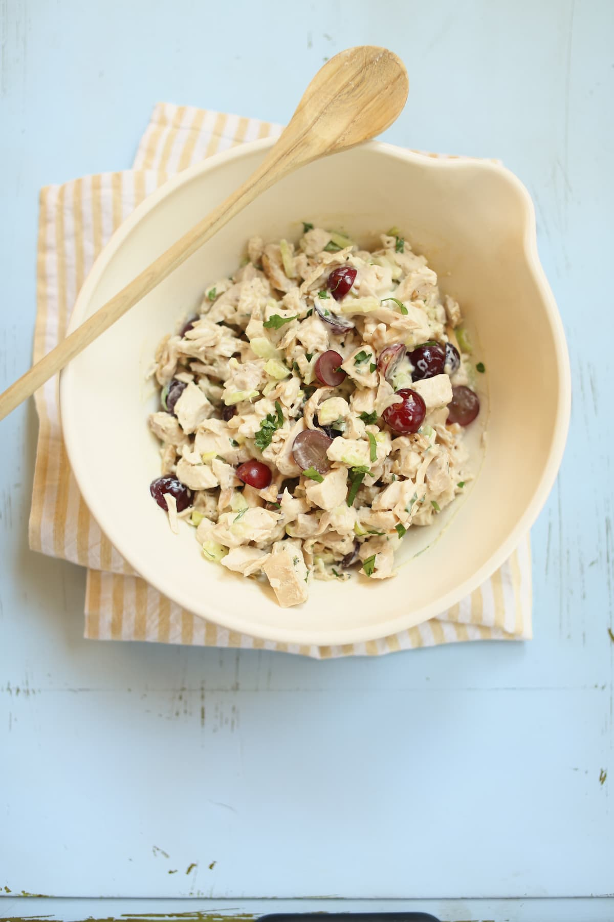 a white bowl of chicken salad with a wooden spoon.