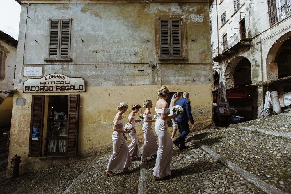 A wedding bridal party walking up to the Santa Maria Assunta Church in Lake Orta a moment before the wedding ceremony . Image by DT studio - Italian wedding photographer