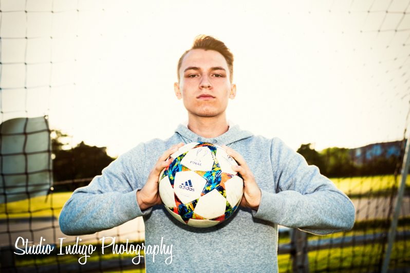 Senior picture of Alex from Verona High School standing in the goal holding a soccer ball.  Shot this with stong backlight from the sun and speedlite set on manual.  I really love this high key, fashion look with the speedlite blasting the subject with specular light.
