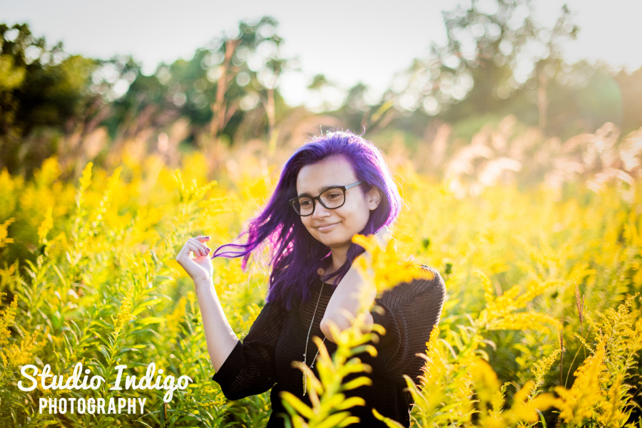 sunny backlit senior picture with girl walking through tall grass