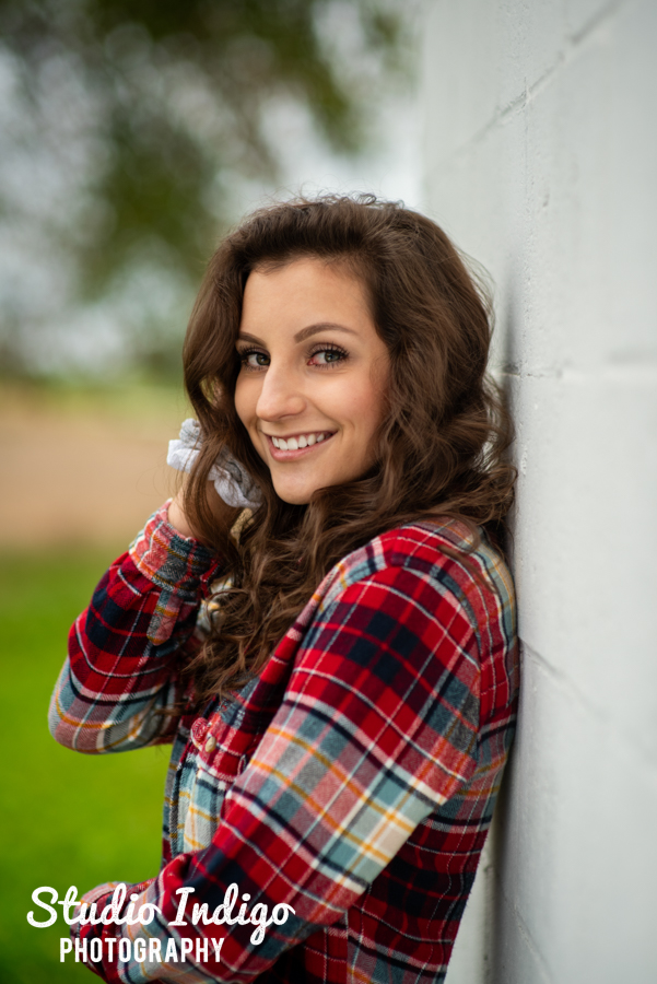 Portrait of high school senior girl wearing red flannel, smiling and leaning against a white wall