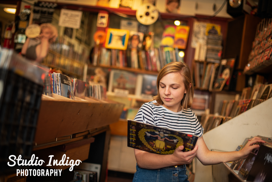 High school senior portrait of girl kneeling in a vintage records store