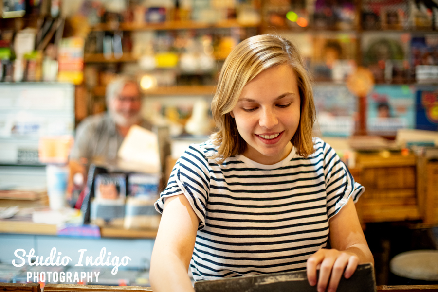 Senior yearbook picture of girl looking through vintage records at madison b-side records on Atwood Ave.