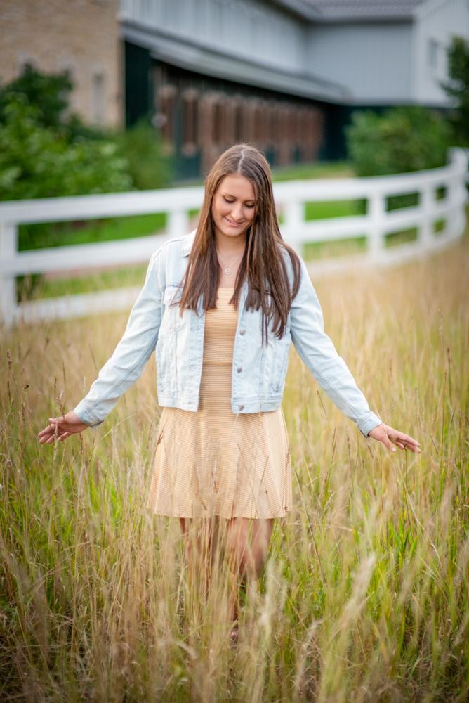 High school senior picture of girl walking through tall grass