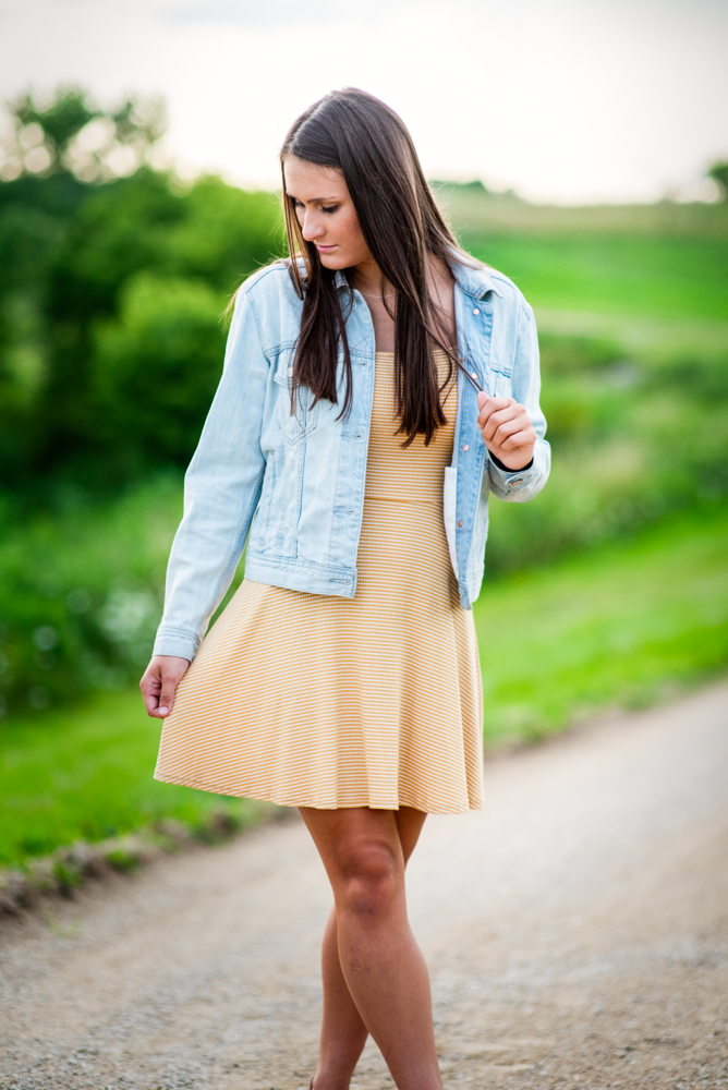 High school senior picture of girl standing on country road looking down