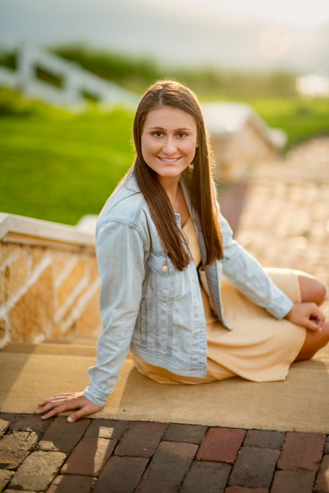 High school senior picture of girl sitting on steps with sunset in the background