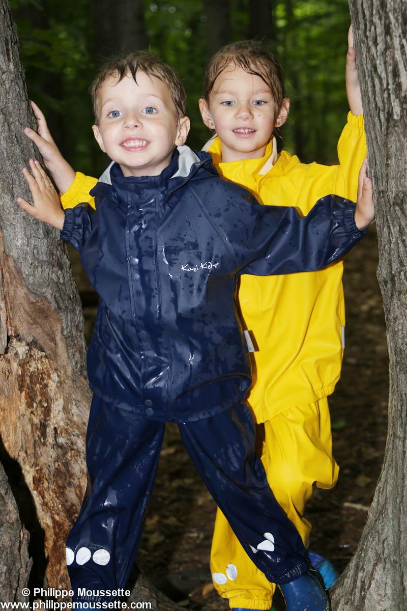 Deux enfants avec un imper dans un arbre