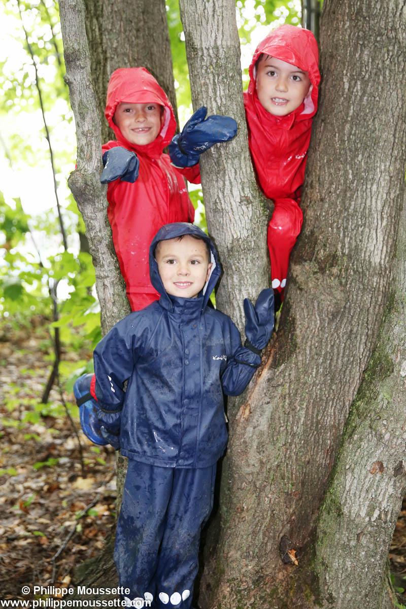 Trois enfants avec imper grimpé dans un arbre