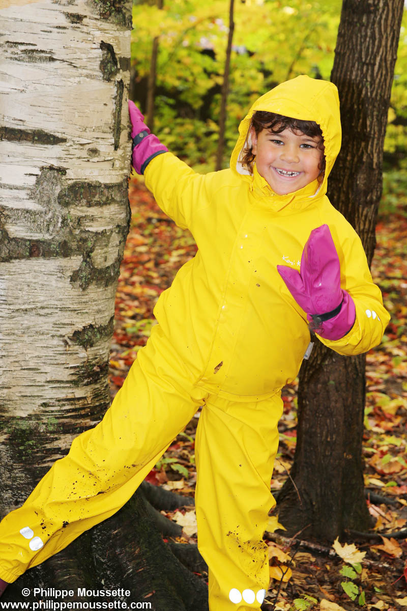 Fille avec un imper jaune dans le bois