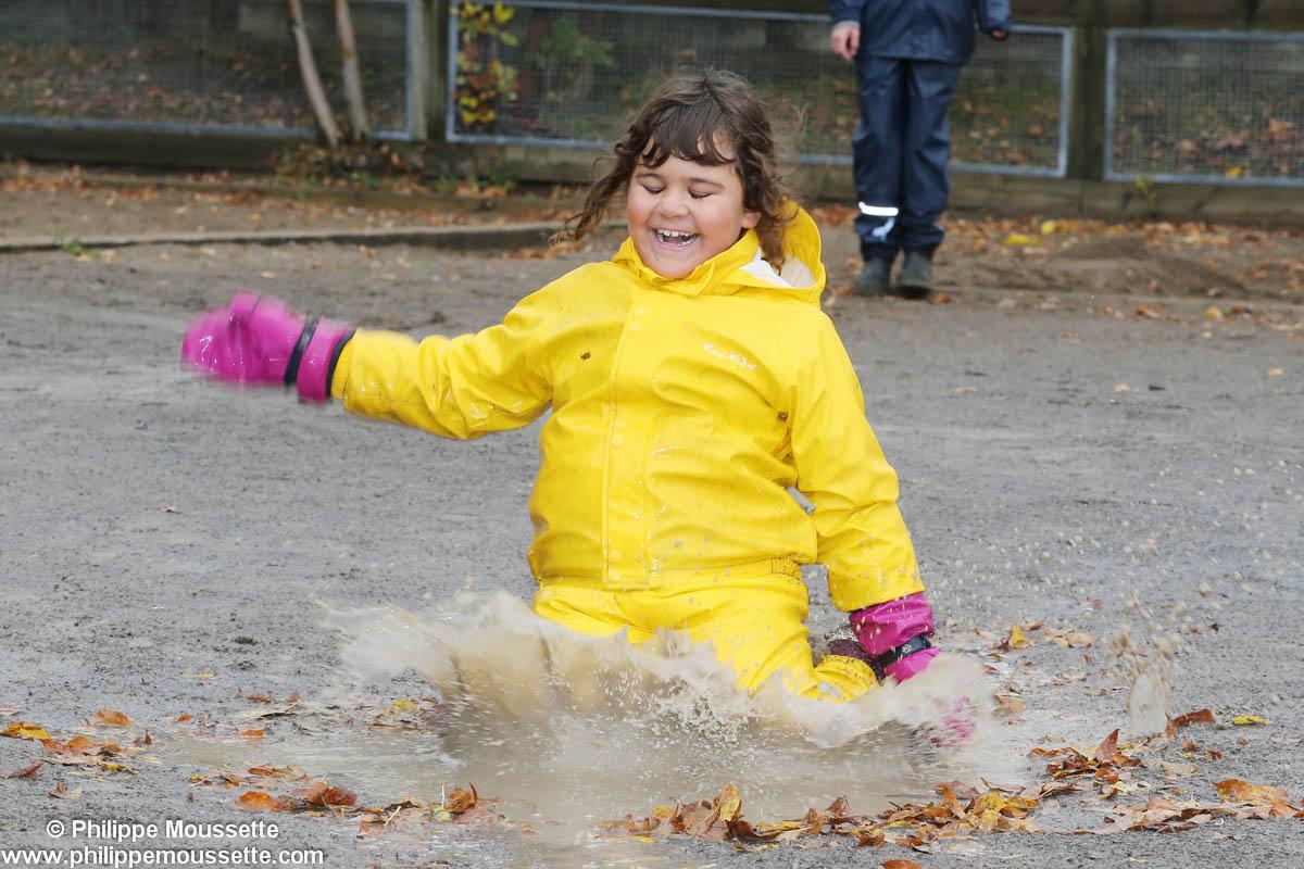 Fille avec un imper jaune dans la boue