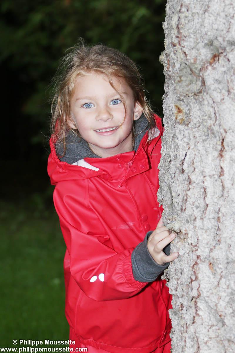 Fillette avec imper rouge derrière un arbre