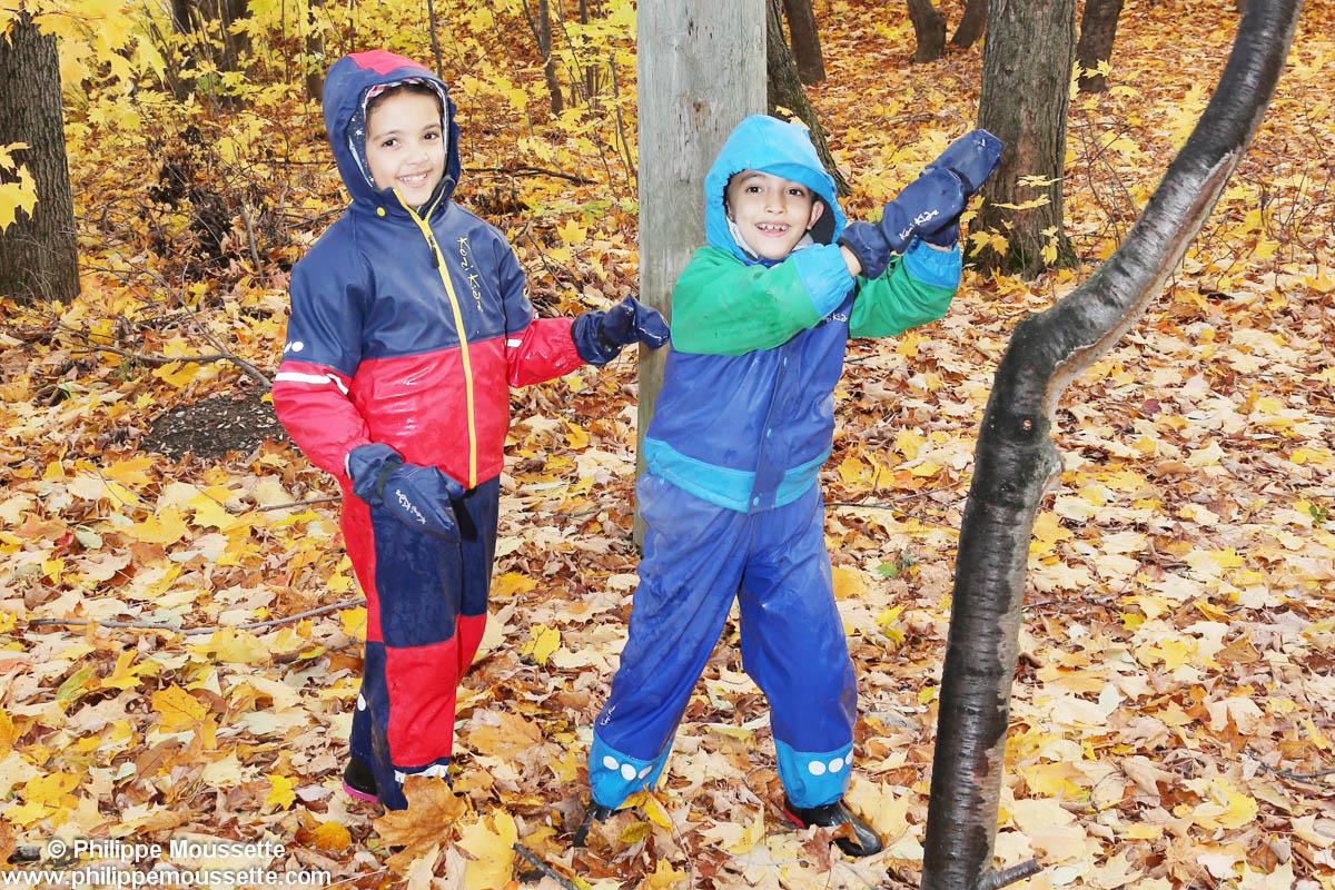 Deux enfants avec imper dans la forêt