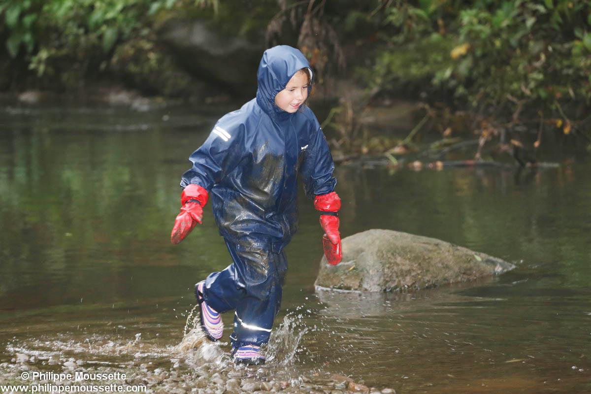 Enfant avec imper dans l'eau