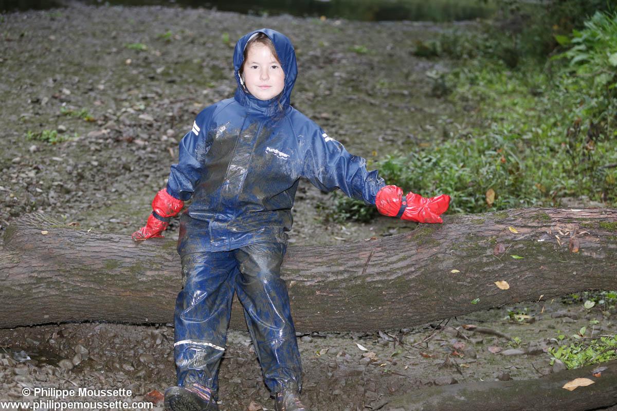 Enfant avec imper recouvert de boue