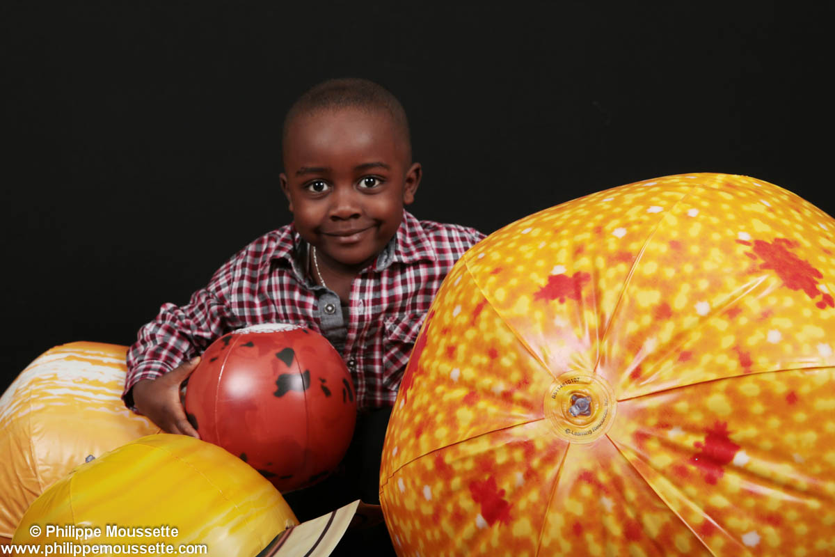 Garçon avec ballons en forme de planètes
