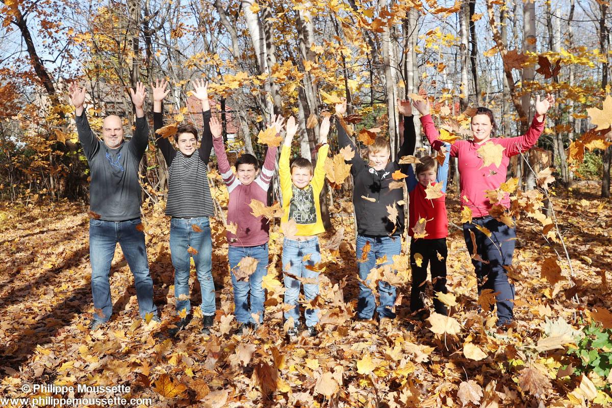 Famille qui lance des feuilles d'automne