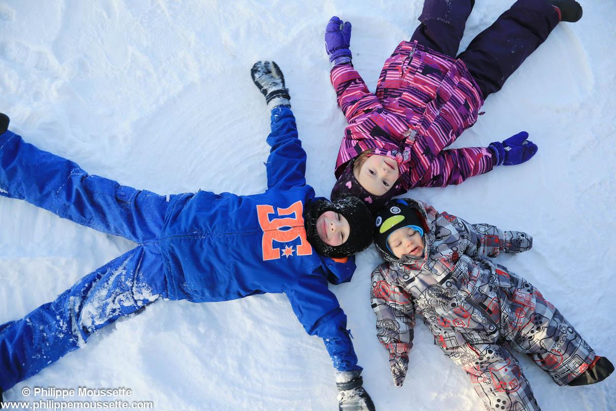 Trois enfants qui font l'étoile dans la neige