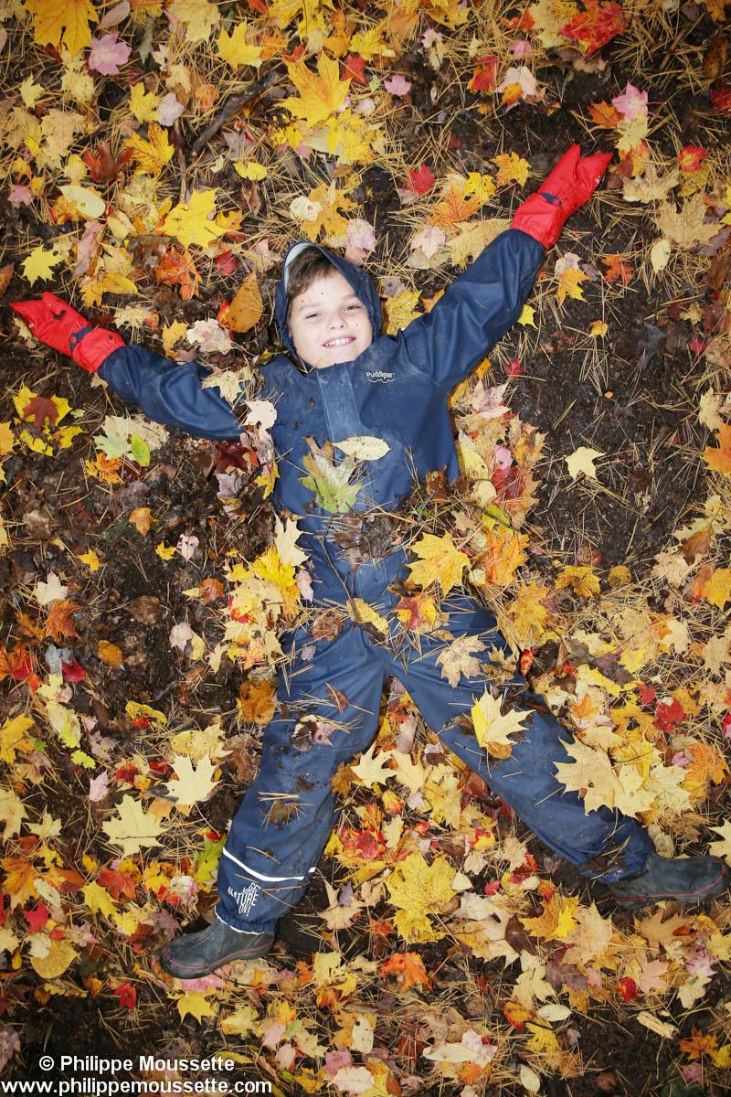 Enfant couché dans les feuilles d'automne