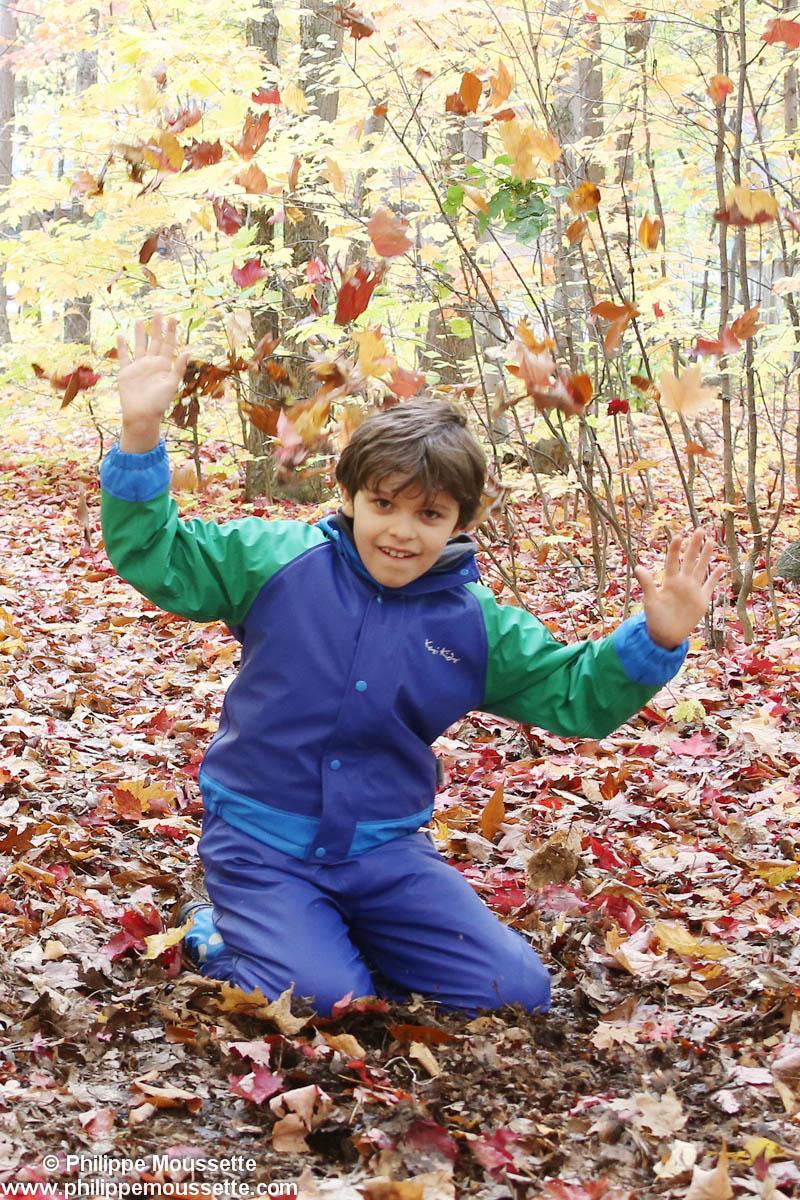Enfant qui lance des feuilles d'automne