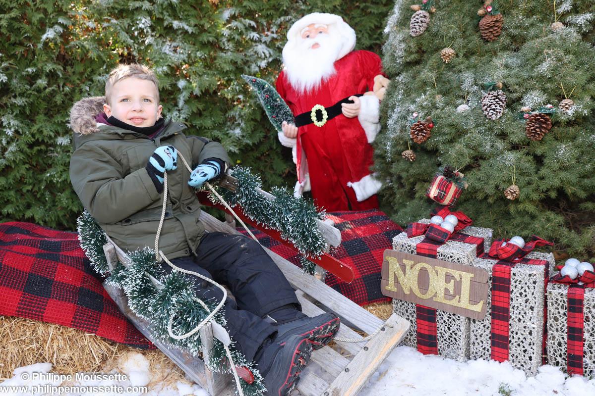 Enfant sur une luge dans un décor de Noël