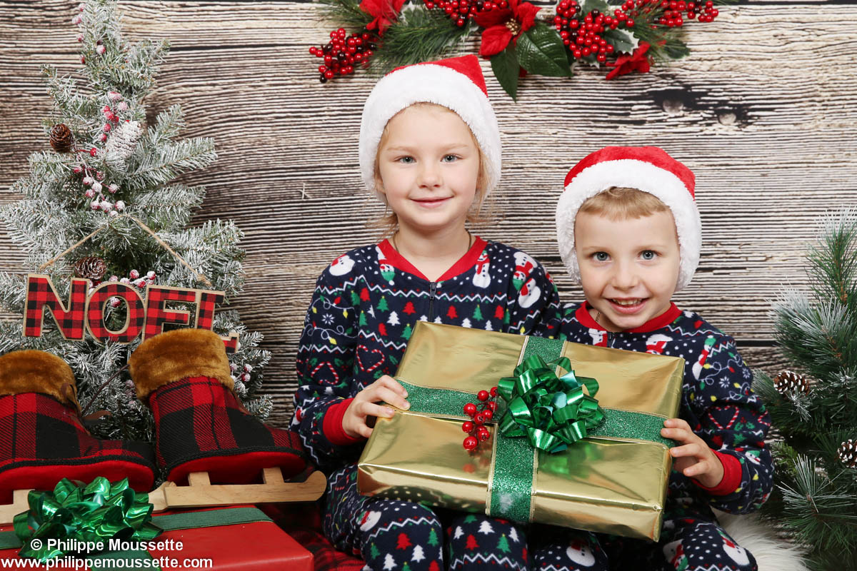 Deux enfants en pyjama de Noël avec un cadeau