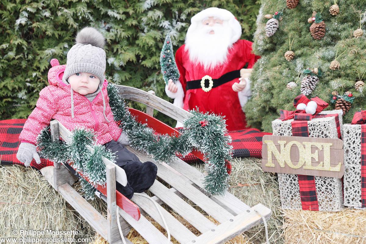 Bébé dans une luge dans un décor de Noël