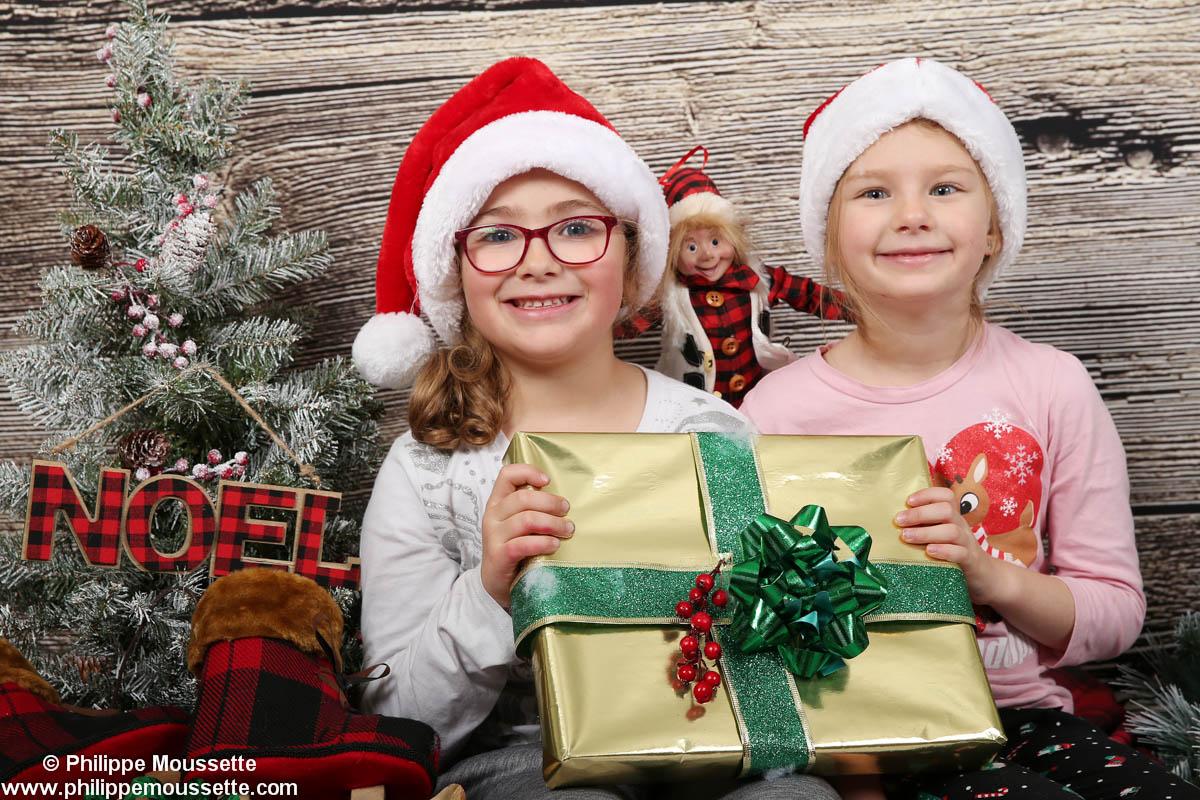 Deux fillettes avec une tuque de Noël et un cadeau