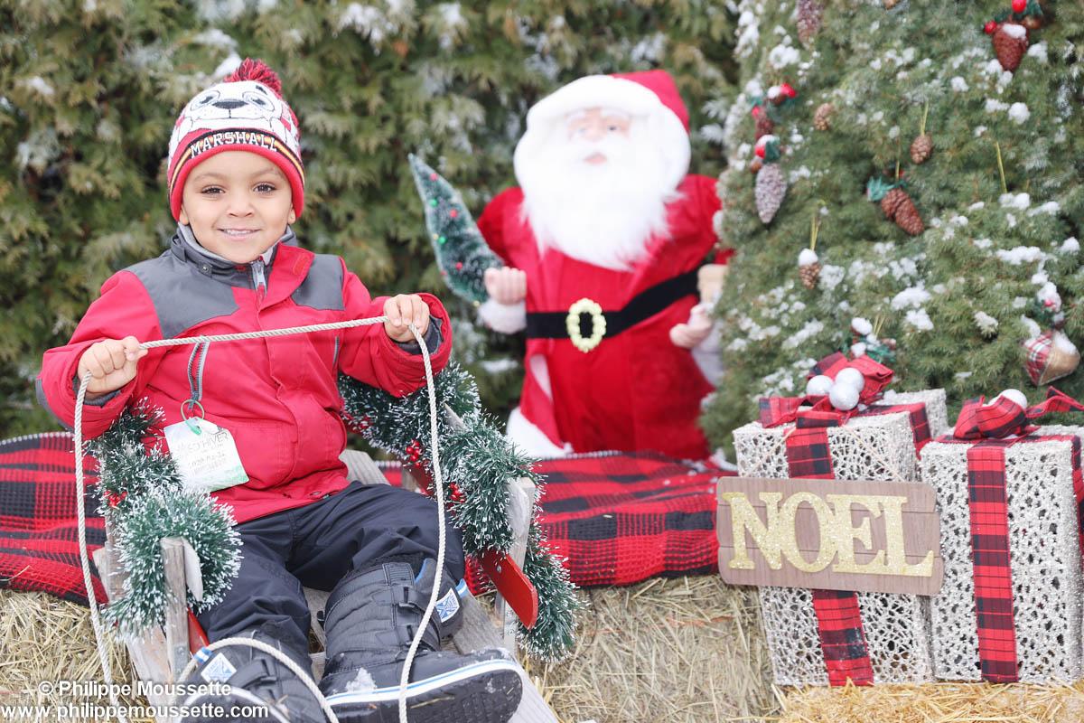 Enfant sur luge dans un décor de Noël