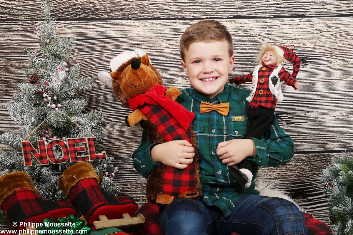 Garçon avec deux toutous dans un décor de Noël