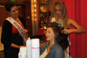 Studio Savvy Glamsquad stylists Mariah Meerschaert and Victoria Sexsmith curling the model's hair for the runway show at the San Diego Wedding Party Expo.