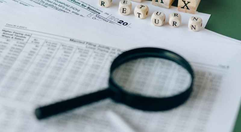 magnifying glass on top of tax documents
