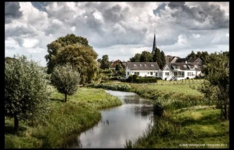 Riviertje richting dorp Everdingen langs de lek met mooi groen landschap en wolkenlucht.
