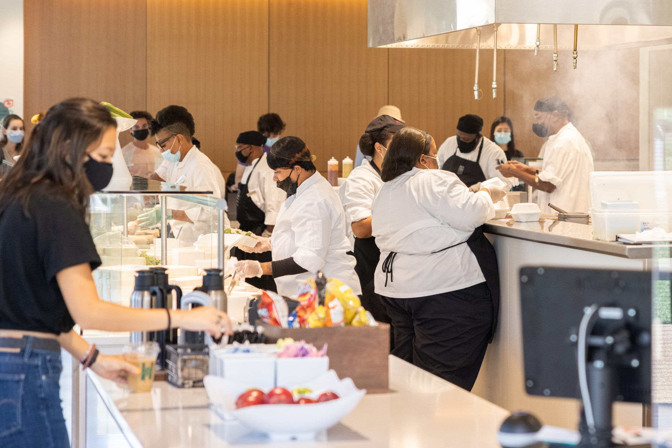 Several chefs in white shirts and black aprons prepare food.