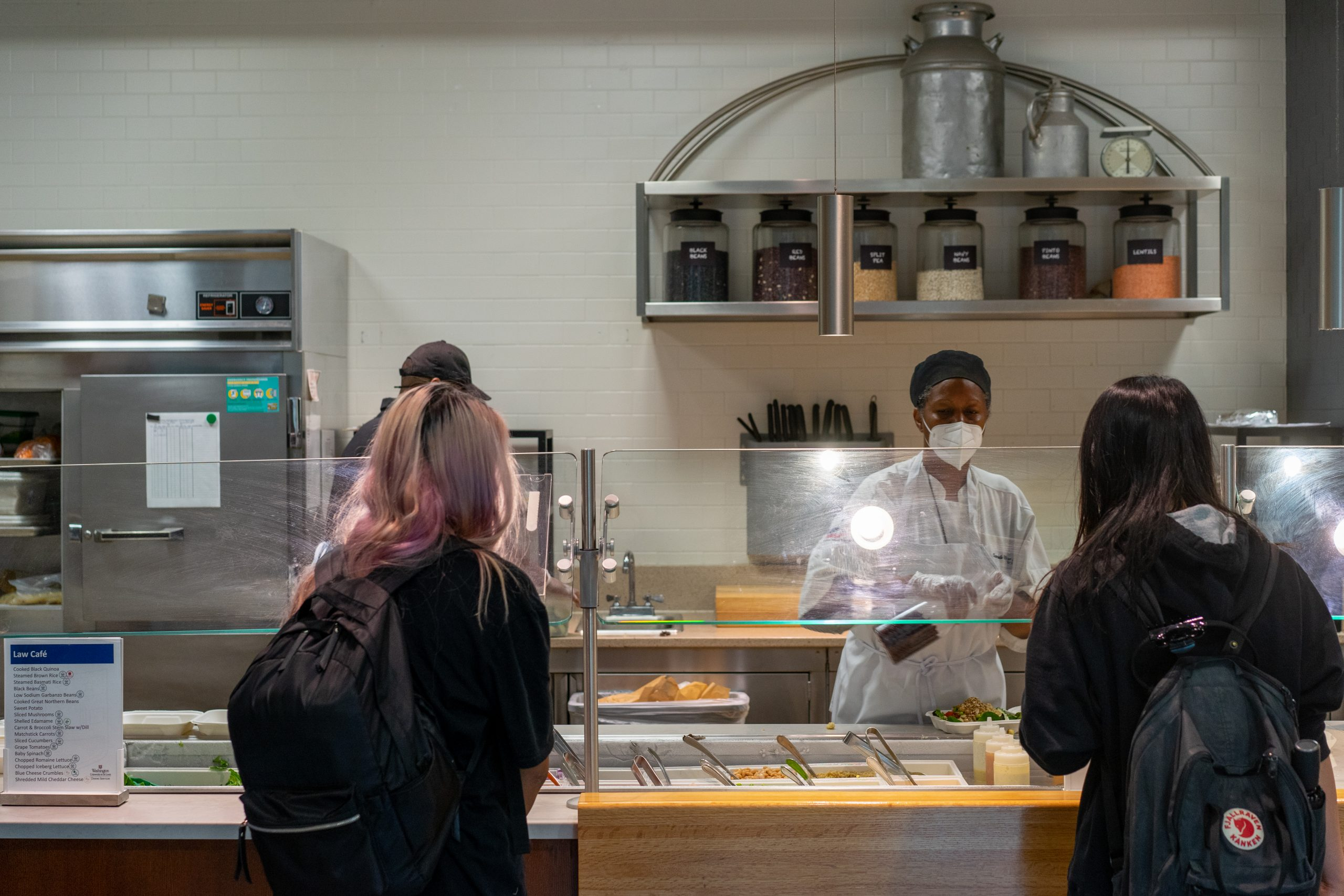 Two students carrying backpacks stand across a counter from a chef.