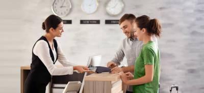 receptionist helping 2 customers