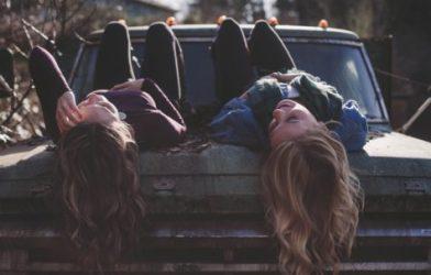 Teen or millennial girls laying on car hood