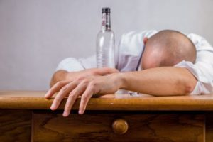 Drunk man passed out with bottle of alcohol