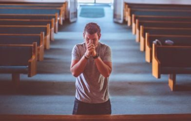 Man praying inside church