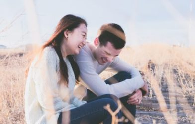 Couple sitting in field laughing