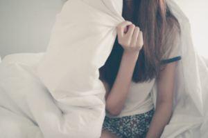 Teen girl hiding under covers