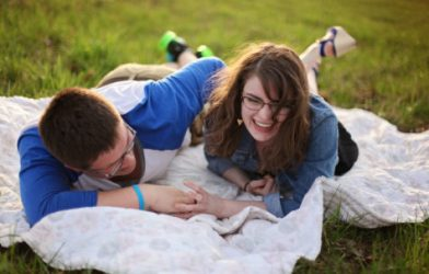 Couple on picnic blanket laughing