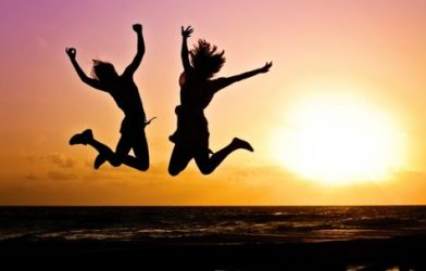 Girls jumping up in the air in front of sunset