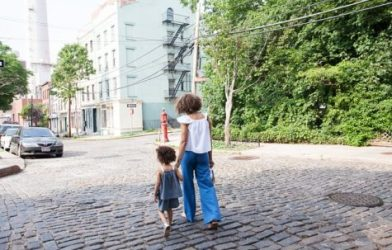 Woman walking in street with child