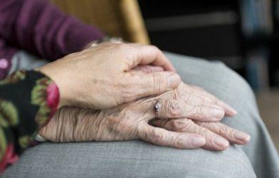 Elderly person's hands being held